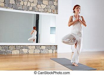 Yoga one leg balance Tree pose on wooden floor