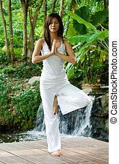 A young woman doing yoga outside