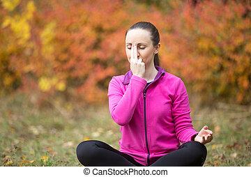 Yoga outdoors: Alternate Nostril Breathing - Portrait of...
