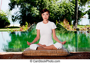 Yoga Outside - A beautiful Chinese woman sitting in a yoga...