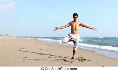 Yoga  - Peaceful fit man practicing yoga on beach