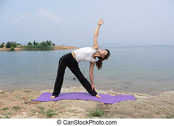 a female fitness instructor demonstrates a yoga pose