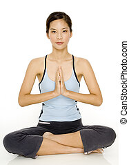 Yoga Pose - A pretty young asian woman in a meditative yoga...