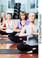 yoga pose - Group of young women in the gym center. Yoga.