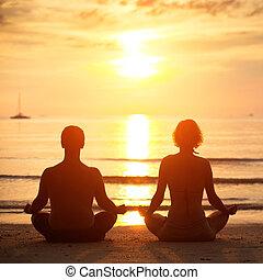 yoga, practice:, un, pareja joven, sentado on the beach, de, el, mar, en, el, posición lotus, en, sunset.