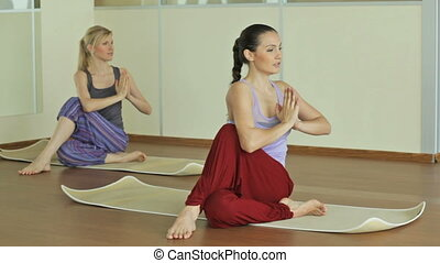 Yoga practice - Two beautiful women practicing yoga indoors