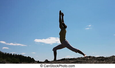 Yoga practice - Young woman practicing yoga outdoors, only...