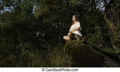 Yoga practitioner doing breathing exercise in the woods nature