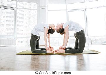 yoga, relajado, dos, flexibilidad, estudio, entrenamiento, mujeres