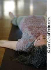 Middle aged female in a yoga pose savasana; resting pose or corpse pose ued at the end of a hatha yoga practice to create deep relaxation in the body and mind.