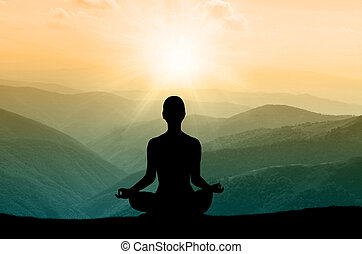 Yoga silhouette on the mountain in sunrays. the dawn sun
