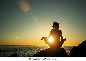 Yoga silhouette young woman on the beach amazing sunset.