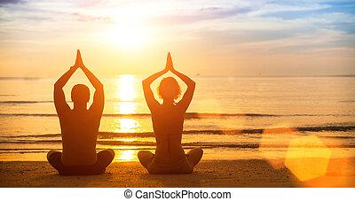 yoga, silueta, de, un, pareja joven, en la playa, en, sunset.