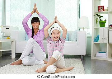 Yoga - Portrait of little girl and her mother doing yoga...