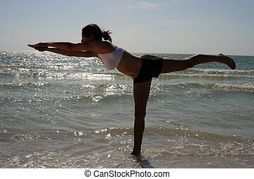 Yoga - Backlit photo of a woman doing yoga on the beach