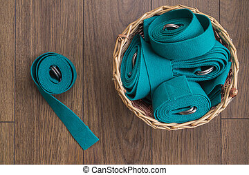 Yoga straps in a wicker basket