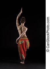 Yoga. Studio photo of topless woman doing asana, back to...