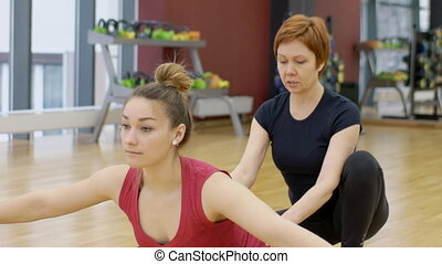 Yoga teacher in training helps to make a woman poses asanas for balance.