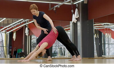 Yoga teacher is in practice with young woman in modern...