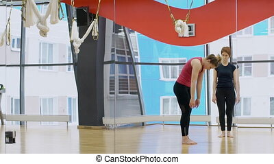 Yoga teacher watches as woman slowly lifts her body in large gym.