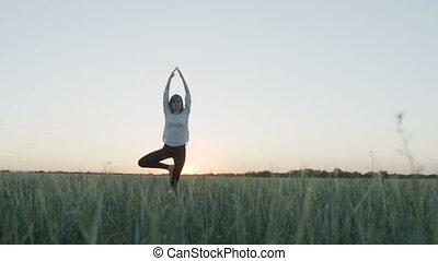 Yoga vrikshasana tree pose by woman at sunset