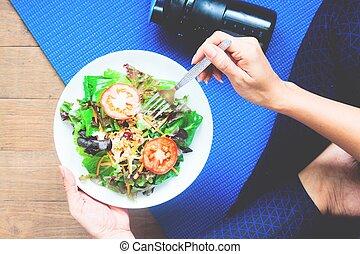 Yoga woman eating fresh salad, Fitness and Healthy concept