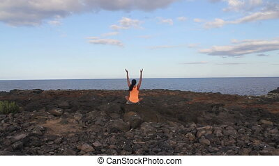 Yoga woman on a beach rock