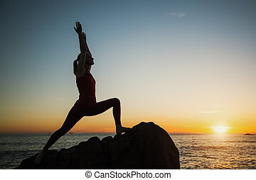 Yoga woman silhouette on the Sea beach at sunset.