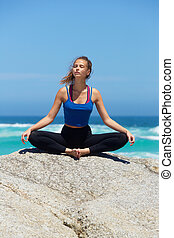 Yoga woman sitting by the sea