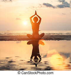 Yoga woman sitting in lotus pose on beach during sunset, with reflection in water (in bright colors)