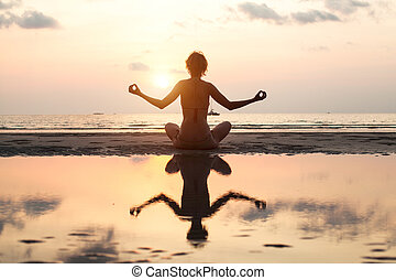 Yoga woman sitting in lotus pose on the beach during sunset, in bright colors, with reflection in water.