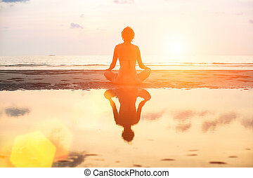 Yoga woman sitting in lotus pose on the beach during sunset, in bright colors with reflection in water.