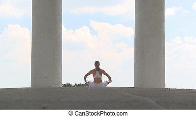 Yogatemple 003 - woman practising yoga between two pillars