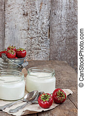 yoghurt in a glass and a bucket with fresh strawberries on a wooden background