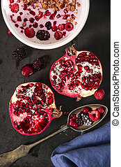 Yoghurt with cereals and fresh forest fruits and sliced pomegranate.
