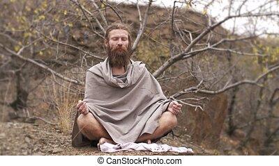 Yogi asket meditating on nature