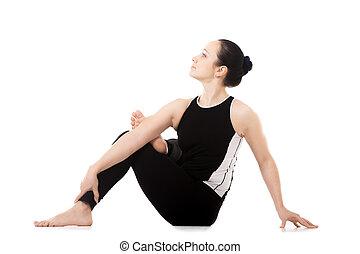 yogi female in yoga asana parivritta eka pada