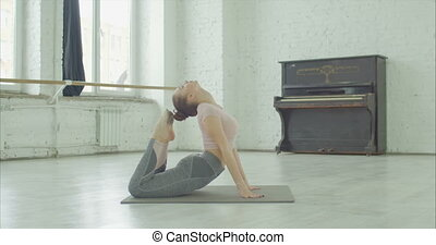 Graceful sporty fit woman practicing yoga, doing cobra and king cobra exercise, Raja bhudjangasana pose, working out on exercise mat in dance studio during stretching and warming up before rehearsal.