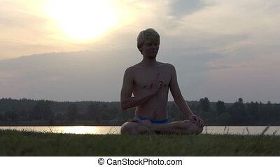 Yogi sits in a lotus, keeps his hand on a chest at sunset in slo-mo