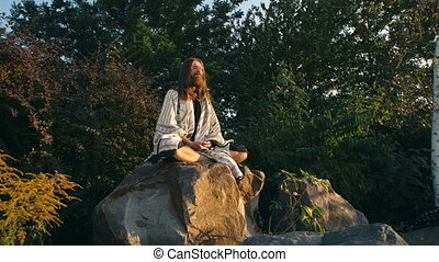 Yogi sitting on the rock and meditating - Yogi sitting in...