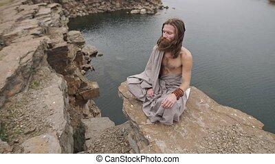 Yogi sitting on the rock near the lake