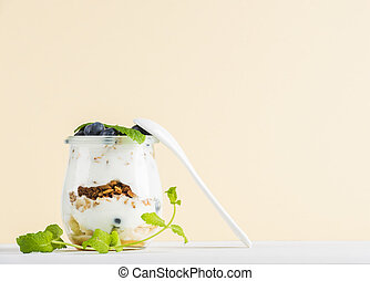 Yogurt oat granola with jam, blueberries and green leaves in glass jar on pastel yellow backdrop, copy space