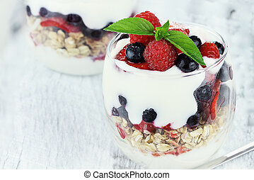 Delicious and healthy yogurt parfait made with Greek yogurt, fresh berries and mint. Extreme shallow depth of field.