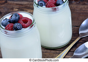 Yogurt with berries in a jars glass
