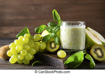 yogurt with fresh kiwi, Apple, green grapes,  spinach and mint on a wooden