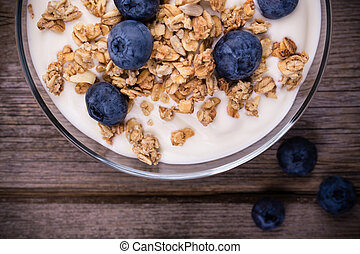 Yogurt with granola and fresh blueberries, in glass bowl over old wood background. Vintage effect.