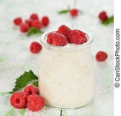 Yogurt with raspberries on a white table