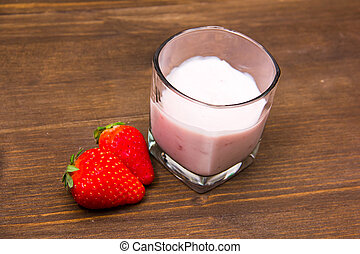 Yogurt with strawberries on wooden table seen from above