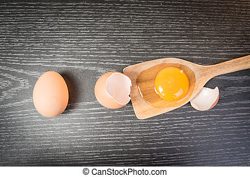 Yolk in wooden spoon on wooden background