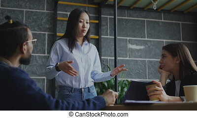 Yong asian woman talking and discussing new ideas with creative team during brainstorming of start-up projects in modern office indoors